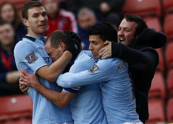Manchester City's Pablo Zabaleta (2nd L) celebrates his goal against Stoke City with Edin Dzeko (L) Sergio Aguero (2nd R) and a fan.