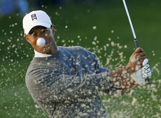 U.S. golfer Tiger Woods hits from a sand trap on the fifth hole during weather delayed fourth round play at the Farmers Insurance Open in San Diego, California January 27, 2013.