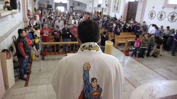 Priest Humberto Álvarez presides over a Mass for children in Ojo de Agua, in Saltillo, México, with a robe decorated with images of superheroes.