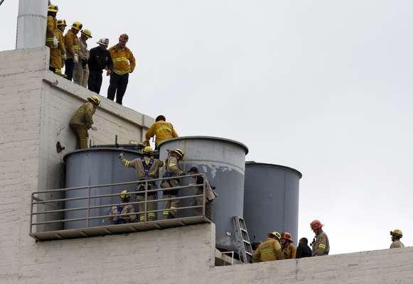 Bombeiros trabalham para remover o corpo encontrado dentro de uma das caixas d'água do hotel na terça-feira