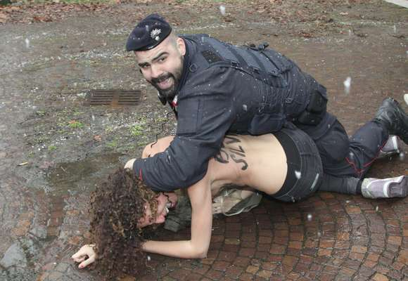 Um policial prende uma manifestante seminua que protestava aos gritos de Basta Berlusconi contra o ex-premiê italiano Silvio Berlusconi durante as eleições que ocorrem neste domingo, na Itália