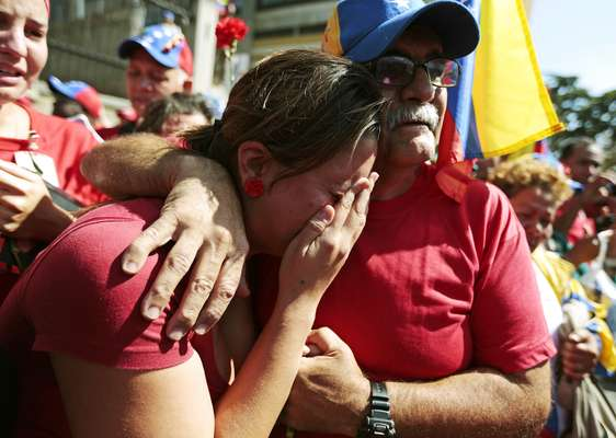 Supporters of late Venezuelan President Hugo Chavez react as his coffin is driven through the streets of Caracas, March 6, 2013. Chavez died on Tuesday of cancer, and authorities have not yet said where he will be buried after his state funeral on Friday. REUTERS/Jorge Dan Lopez (VENEZUELA - Tags: POLITICS OBITUARY)