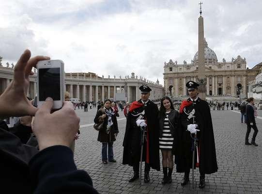 Una turista posa para una foto de recuerdo con dos carabineros con uniforme de gala que patrullan por la Plaza de San Pedro de Roma