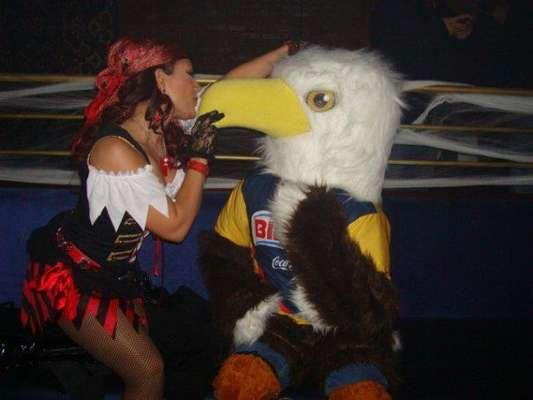 Diana Reyes disfrazada como una sensual pirata besa y seduce a una persona caracterizada como un pajarito en pleno concierto.