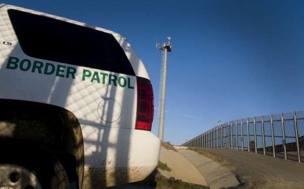 El patrullero fronterizo detiene el coche en la cima de una colina, del lado estadounidense, y señala hacia un barrio popular de la ciudad mexicana de Tijuana, separada de California por un muro en el que, según activistas, murieron 10.000 personas.