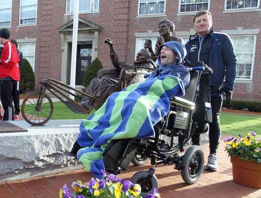 Dick Hoyt y su hijo Rick posan junto a la estatua de bronce inaugurada recientemente en su honor, en la previa de la maratón de 2013.