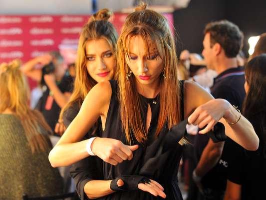 Modelos se aprontam em backstage antes de desfilar