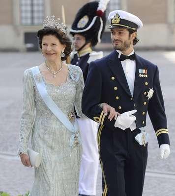 La reina Silvia, madre de la novia, llevaba un vestido de color jade. El vestido es de organza de seda bordada y cristales de Swarovski. Este fue acompañado de la tiara de la reina Sofía y un collar de brillantes con la gota. La soberana ha llegado a la capilla del Palacio Real acompaña de su hijo, el príncipe Carlos Felipe.