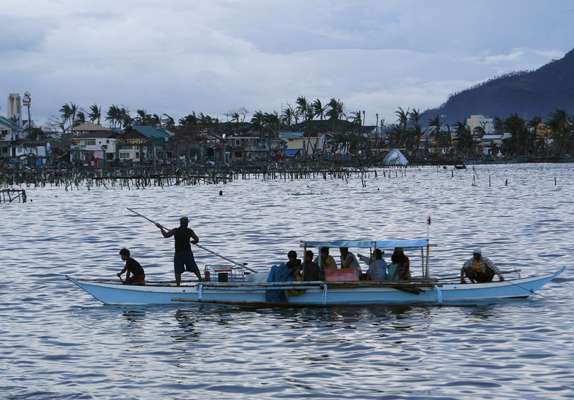 People leave on a boat against the backdrop of a destroyed fishing community after the Super typhoon Haiyan battered Tacloban city in central Philippines November 12, 2013. Philippine officials have been overwhelmed by Super Typhoon Haiyan, one of the strongest on record, which tore through the central Philippines on Friday and flattened Tacloban, coastal capital of Leyte province where officials fear 10,000 people died, many drowning in a tsunami-like wall of seawater. REUTERS/Edgar Su (PHILPPINES - Tags: DISASTER ENVIRONMENT MARITIME)