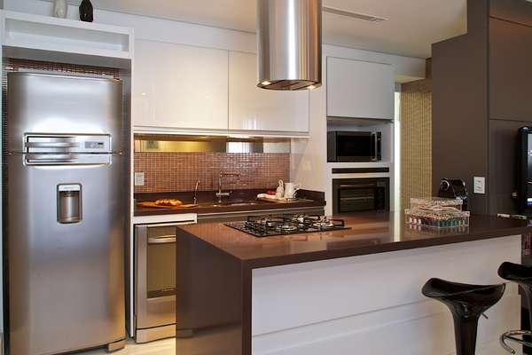 A cozinha americana de 7m², projetada pela arquiteta Cinthia Garcia e a designer Andréia Karalkovas, conta com cores neutras e faixa de pastilhas metalizadas para contrastar com a sala. Apresenta coluna para o forno e micro-ondas, além de bancada com cook top. Informações: (11) 4224-2000