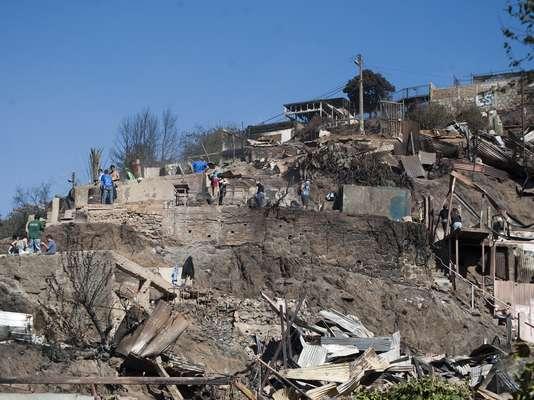 Cientos de vecinos del Cerro La Cruz trabajan en la zona removiendo los escombros que dejó el brutal incendio que afectó a la zona desde la tarde del sábado.