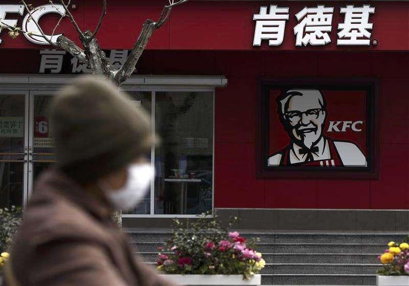 Una mujer con una máscara en el rostro pasa junto a un restaurante de KFC en Shanghái, abr 11 2013. Otra persona murió el jueves debido a una nueva variedad de gripe aviaria en China, dijeron medios estatales, lo que llevó a 10 el número de fallecidos por el virus H7N9, mientras un organismo de la ONU expresó su preocupación de que el virus pueda cruzar las fronteras y propagarse a través de aves de corral. Foto: Aly Song/Reuters