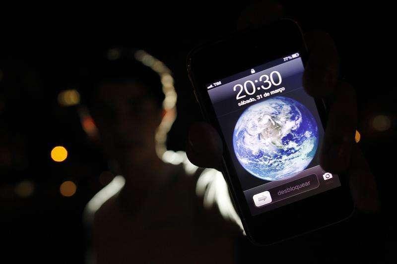 Um homem posa para foto com um iPhone durante a Hora do Planeta no centro de Brasília. De olho no cumprimento da meta de superávit primário deste ano, o Tesouro Nacional pediu para a Agência Nacional de Telecomunicações (Anatel) pensar em maneiras para aumentar a arrecadação com o leilão de serviço móvel de quarta geração (4G) na faixa de 700 megahertz (MHz), previsto para agosto, disse à Reuters uma fonte do governo a par do assunto. 31/03/2012 Foto: Ueslei Marcelino/Reuters