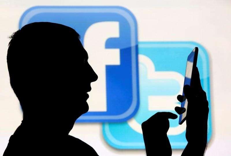 Un hombre usa una tablet mientras se para frente a una pantalla con el logo de Facebook y Twitter en Sarajevo, 22 de octubre de 2013. Los estadios brasileños cuyas obras finalizaron justo antes de la Copa del Mundo están resistiendo bien las multitudes, pero sus redes de telefonía celular muestran signos de colapso. Foto: Dado Ruvic/Reuters