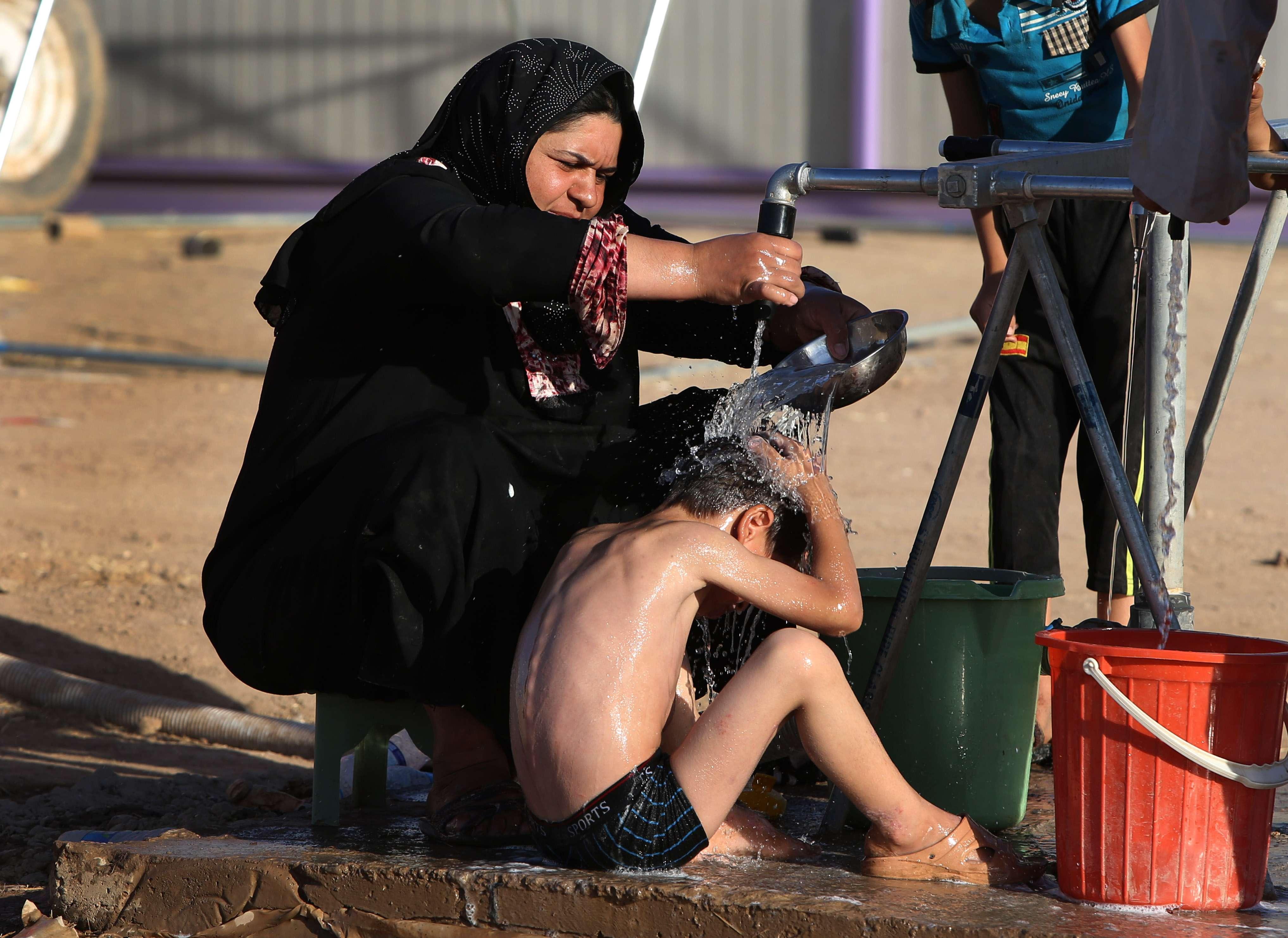 22 de junho - mulher iraquiana banha seu filho em um acampamento para deslocados iraquianos que fugiram de Mossul e outras cidades tomadas pelos insurgentes do Estados Islâmico e do Levante Foto: AP