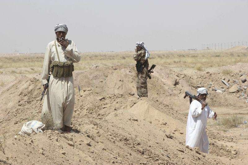 Voluntarios chiíes de pie con sus armas tras asegurar un área predominantemente suní al sur de Bagdad. Fuerzas del Gobierno iraquí iniciaron el sábado una ofensiva para recuperar la ciudad de Tikrit de manos de los militantes suníes, mientras los partidos buscaban una salida que puede poner fin al divisivo Gobierno del primer ministro Nuri al-Maliki. 28 de junio de 2014. Foto: Alaa Al-Marjani/Reuters