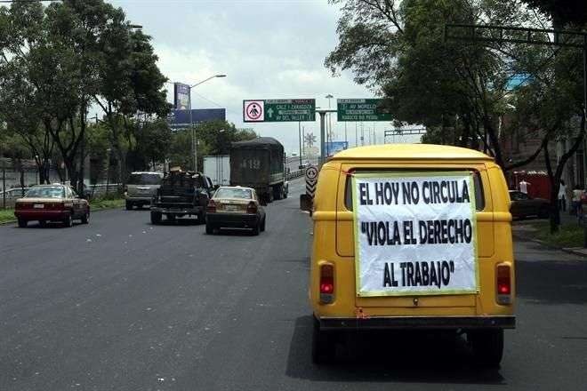 Automovilistas inconformes con los ajustes al Hoy No Circula en el DF colocan mantas con leyendas para mostrar su desacuerdo. Foto: Reforma