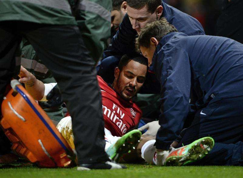Arsenal's Theo Walcott holds shows his agony as he is injured during their English FA Cup soccer match against Tottenham Hotspur at the Emirates stadium in London, January 4, 2014. Foto: Dylan Martinez/Reuters
