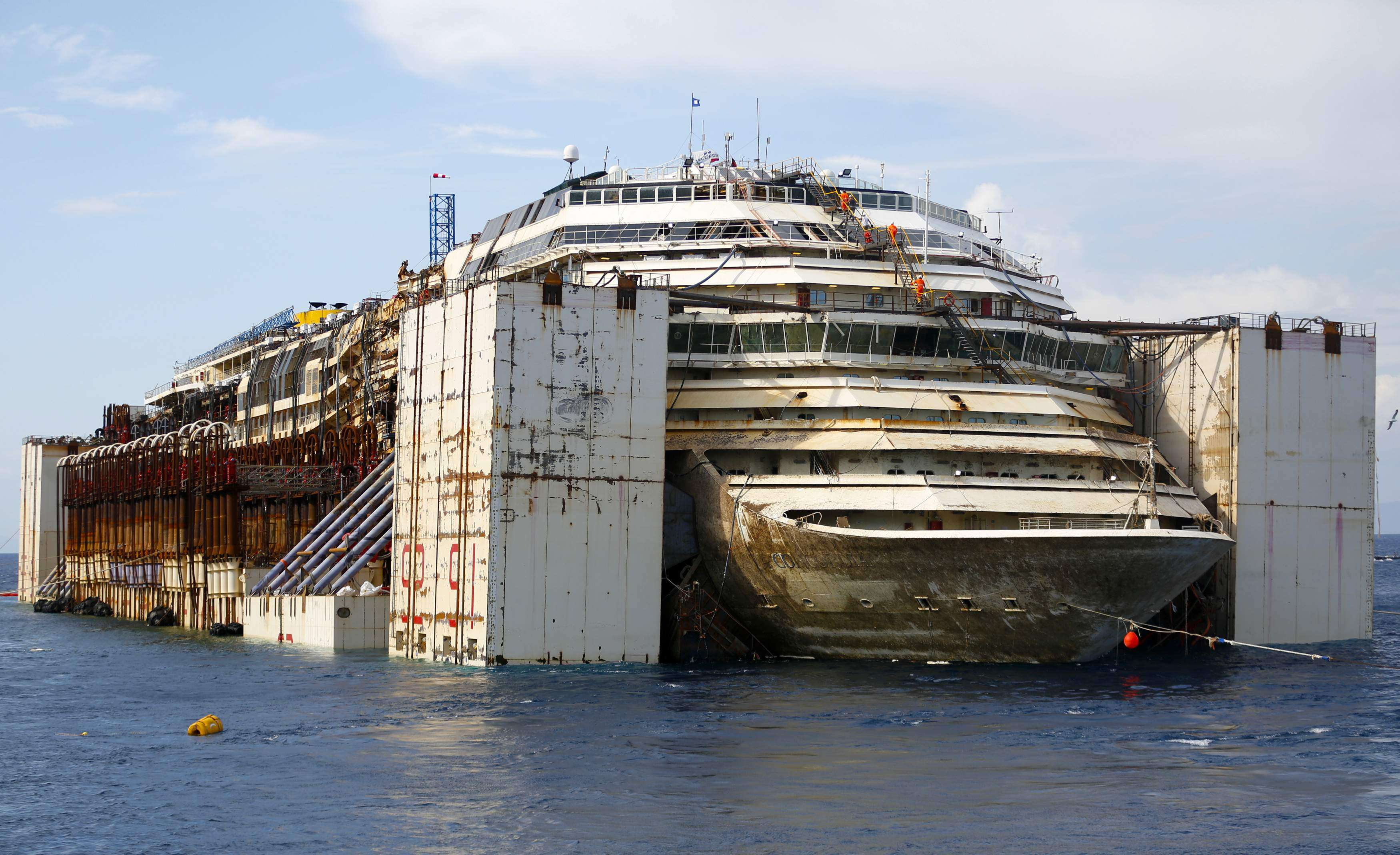 The Costa Concordia cruise liner is seen during its refloat operation at Giglio harbour July 22, 2014. The massive hulk of the Costa Concordia is nearly ready to be towed away from the Italian island where it struck a rock and capsized two-and-a-half years ago, killing 32 people, officials said on Sunday. The 114,500-tonne Concordia has been slowly lifted from the sea floor since Monday, when salvagers began pumping air into 30 large metal boxes, or sponsons, attached around the hull. A convoy of 14 vessels will then tow the Concordia to a port near Genoa, where it will be broken up for scrap, completing one of the biggest maritime salvage operations in history. REUTERS/Max Rossi (ITALY - Tags: DISASTER MARITIME TPX IMAGES OF THE DAY) Foto: MAX ROSSI/REUTERS
