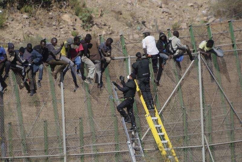 Dos de los inmigrantes encaramados a la valla de Melilla desde esta madrugada se han bajado de la verja y han sido entregados a Marruecos. Los dos subsaharianos han descendido por una de las escaleras colocadas por la Guardia Civil y, posteriormente, fueron entregados a las autoridades marroquíes por una de las puertas de acceso de la valla Foto: EFE en español