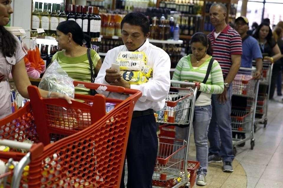 Varias personas hacen fila para pagar en un supermercado en Caracas, Venezuela. El nuevo sistema busca impedir que una misma persona compre el mismo producto en una cantidad que exceda volúmenes.