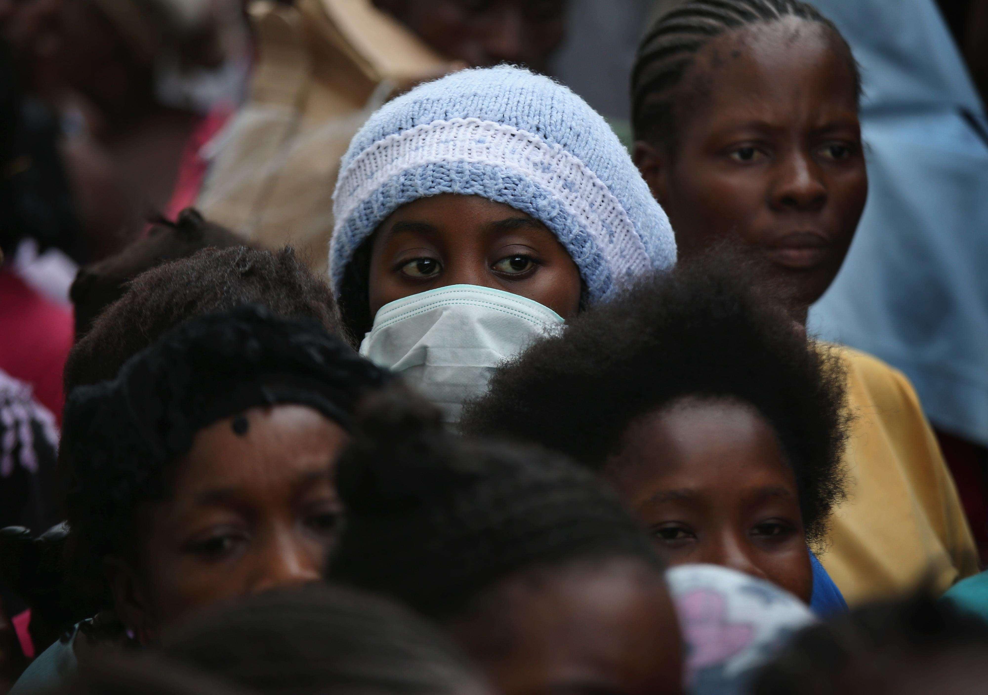 Vecinos de la barriada de West Point, en Monrovia, Liberia, reciben comida durante el segundo día de cuarentena decretada por el gobierno en sus barrios, el 21 de agosto de 2014. Foto: Getty Images