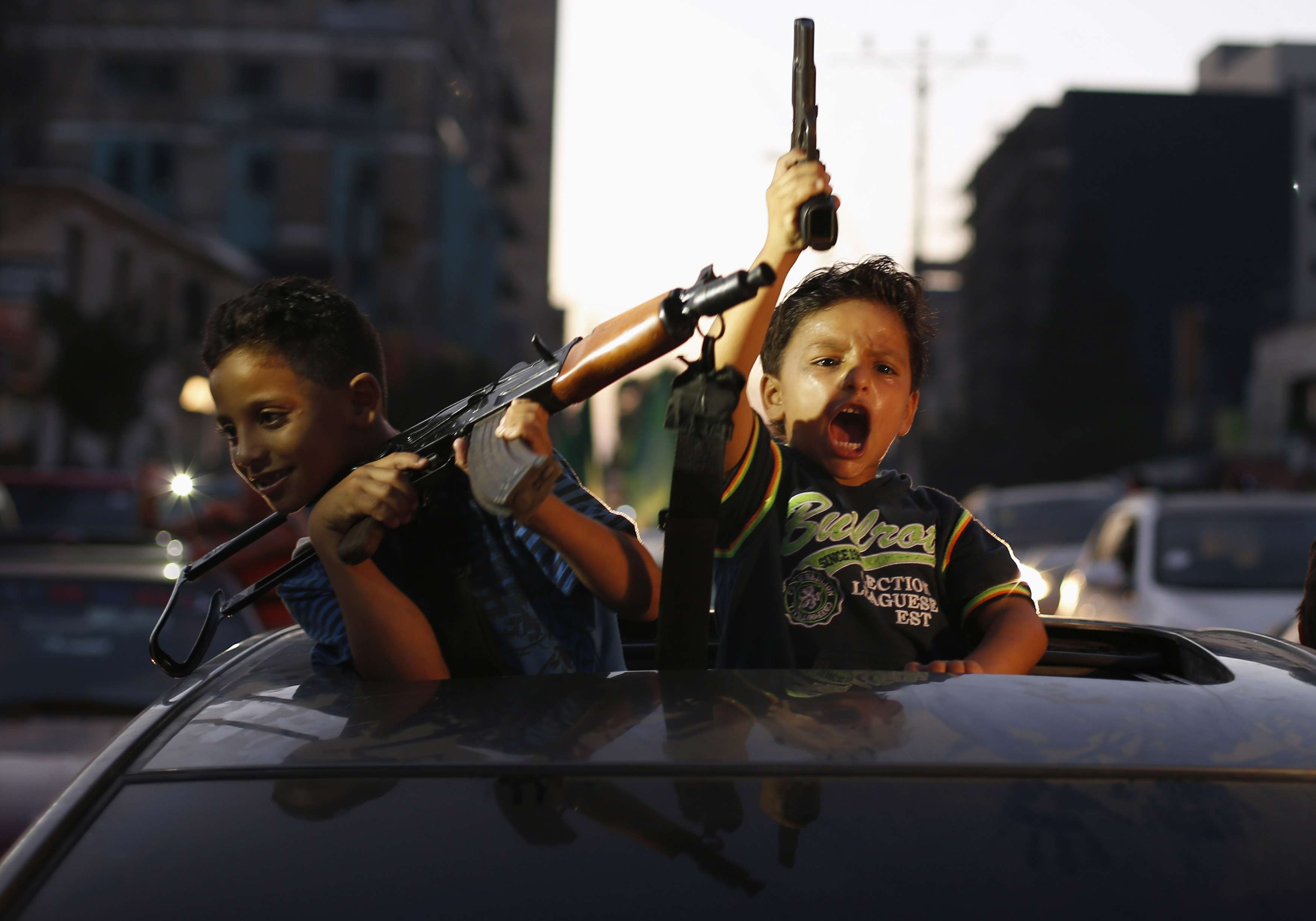 Palestinian children hold guns as they celebrate with others what they said was a victory over Israel, following a ceasefire in Gaza City August 26, 2014. Israel has accepted an Egyptian proposal for a Gaza ceasefire, a senior Israeli official said on Tuesday. Egyptian and Palestinian officials said the truce was to take effect at 7 pm (1600 GMT). REUTERS/Suhaib Salem (GAZA - Tags: POLITICS CIVIL UNREST CONFLICT TPX IMAGES OF THE DAY) Foto: SUHAIB SALEM/REUTERS