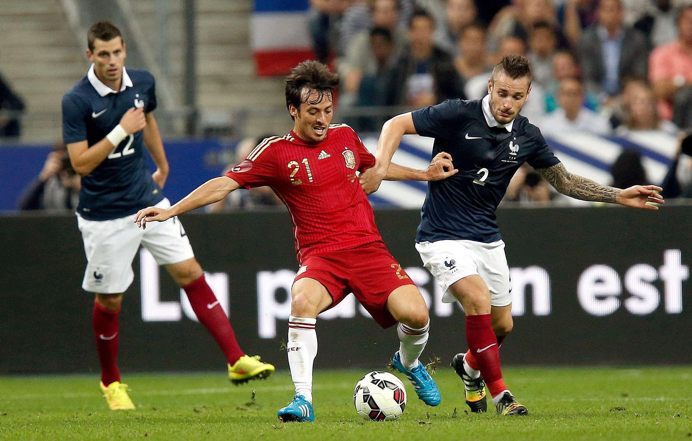 El jugador francés Debuchy (d) pelea un balón con Silva (c), de España, durante el partido amistoso disputado el jueves 4 de septiembre en el estadio de Saint Denis, en París. Foto: EFE