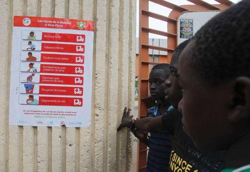 El virus del ébola se está propagando con mucha rapidez en Liberia, donde se esperan varios miles de nuevos casos en las próximas tres semanas, dijo el lunes la Organización Mundial de la Salud (OMS). En la imagen, un grupo de niños observan un cartel con precauciones contra el ébola, durante un entrenamiento de la selección de Sierra Leona en el estadio Felix Houphouet Boigny, en Abidjan, el 5 de septiembre de 2014. Foto: Luc Gnago/Reuters