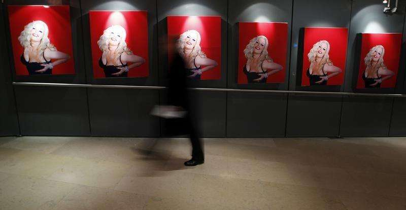 A man walks past posters put up at the Royal Opera House on the opening night of the opera based on the life of Anna Nicole Smith, in central London, February 17, 2011. Foto: Andrew Winning/Reuters