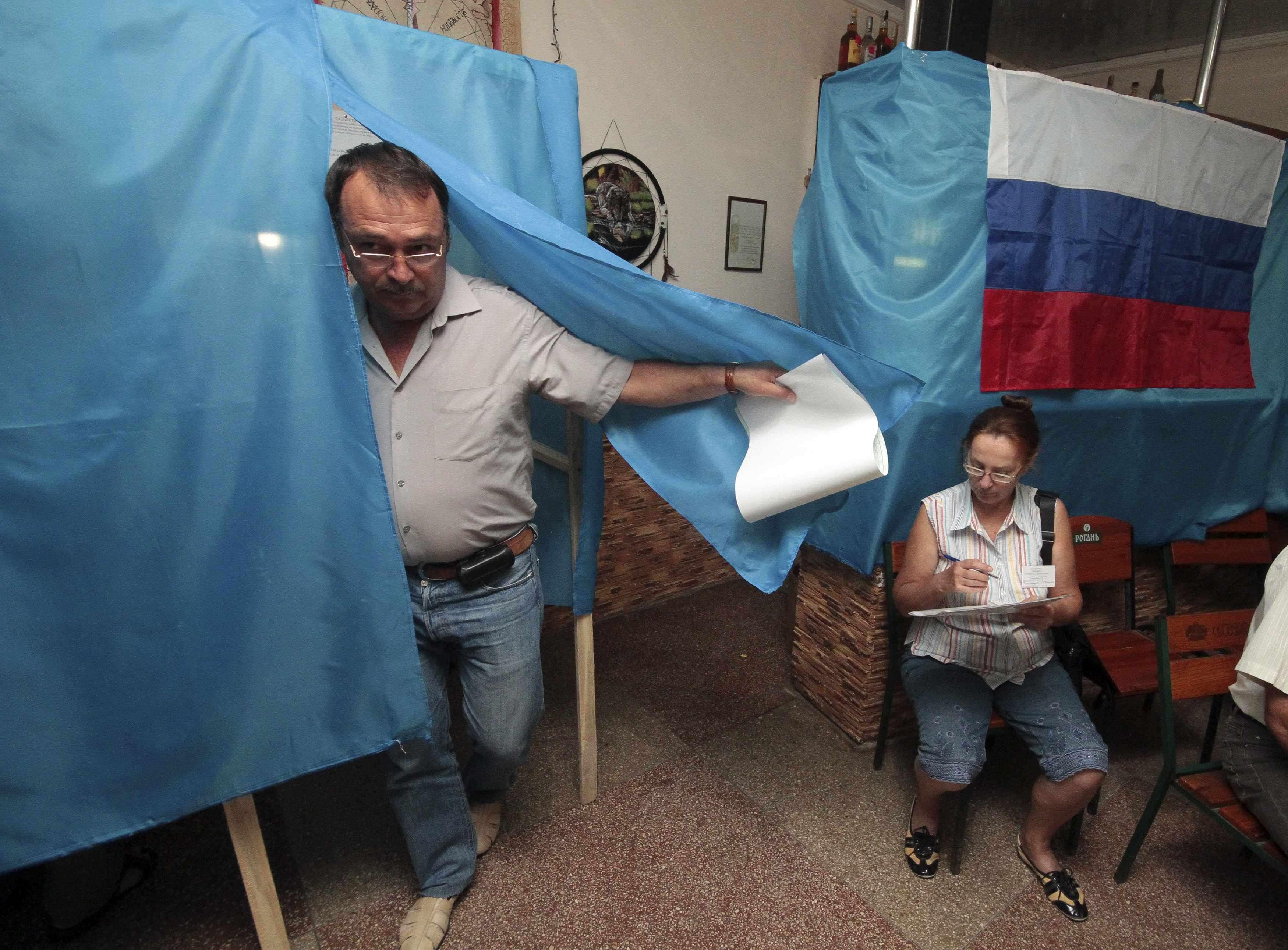 Um homem deixa a cabine de votação na assembleia de voto no porto de Sebastopol da Crimeia, neste domingo, 14 de setembro Foto: Stringer/Reuters