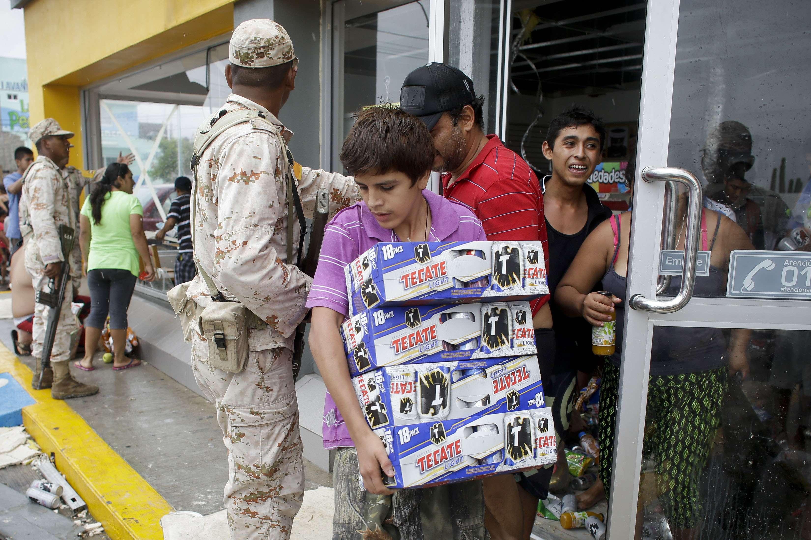 Habitantes de Los Cabos aprovecharon el daño a los comercios por el paso del huracán Odile para saquearlos, aún enfrente de soldados Foto: AP