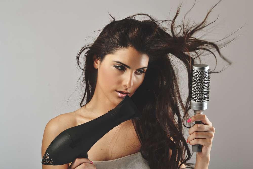 Retirar a umidade dos fios antes de escovar evita que o cabelo receba excesso de calor Foto: studio1901 /Shutterstock