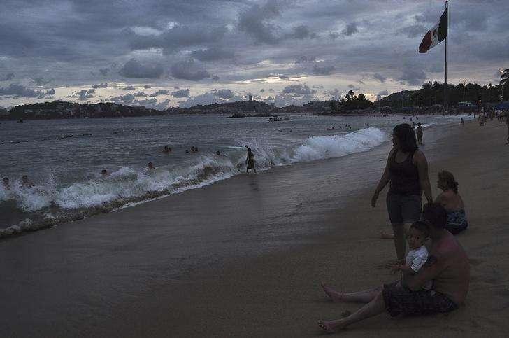 Personas en la playa de Acapulco mientras el huracán Odile se mantiene alejado de las costas, 14 septiembre, 2014. El poderoso huracán Odile causaba el lunes fuertes lluvias, vientos y oleaje en el sur de la Península de Baja California, en el noroeste de México, donde cientos de turistas que visitaban lujosos balnearios se refugiaban en albergues. Foto: Claudio Vargas/Reuters