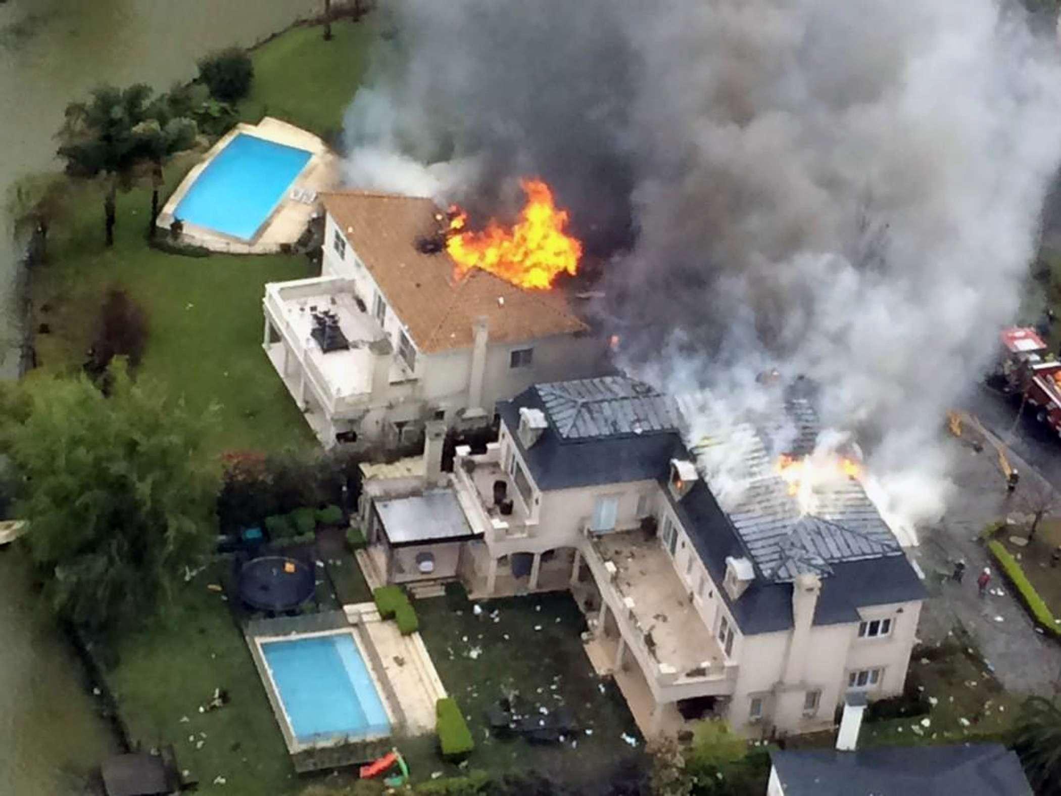 Casas em chamas após um pequeno avião ter caído na cidade de Tigre, na periferia norte de Buenos Aires, na Argentina Foto: AFP