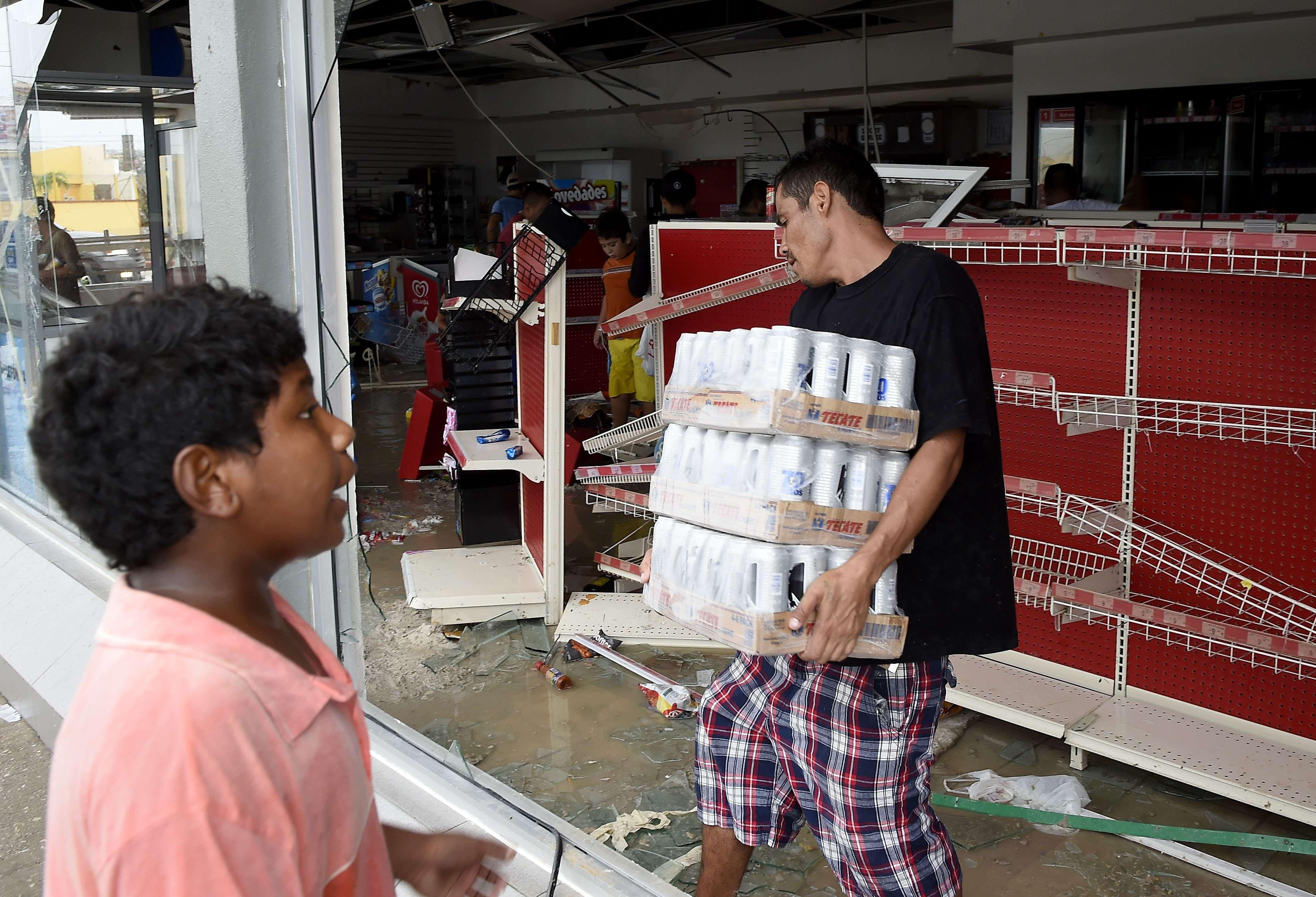 Pobladores han saqueado comida, pilas y bebidas alcohólicas de tiendas de autoservicio Foto: AFP