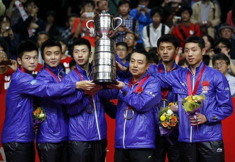 (From L to R) China's Fan Zhendong, Wang Hao, Ma Long, coach Liu Guoliang, Zhang Jike and Xu Xin pose with the world championships trophy on the podium during the medal ceremony after their men's final match victory over Germany at the World Team Table Tennis Championships in Tokyo May 5, 2014. Foto: Toru Hanai/Reuters