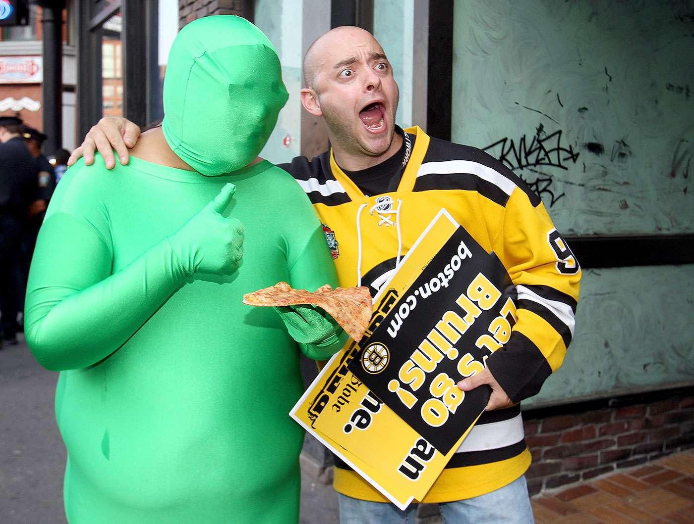 """Las mejores mascotas no oficiales del deporte: Mascota: Green Men. Equipo: Vancouver Canucks. """"Canuck"""" es una forma de llamar a los canadienses, aunque para otros es referencia a las ballenas del norte del continente americano. Los Green Man son unos personajes que molestan a los jugadores y rivales de los Vancouver Canucks cuando están en la caja de castigo durante los juegos de la NHL. Visten con un horrible spandex verde molestando a todos los jugadores que son sancionados. Foto: Jim Rogash/Getty Images"""