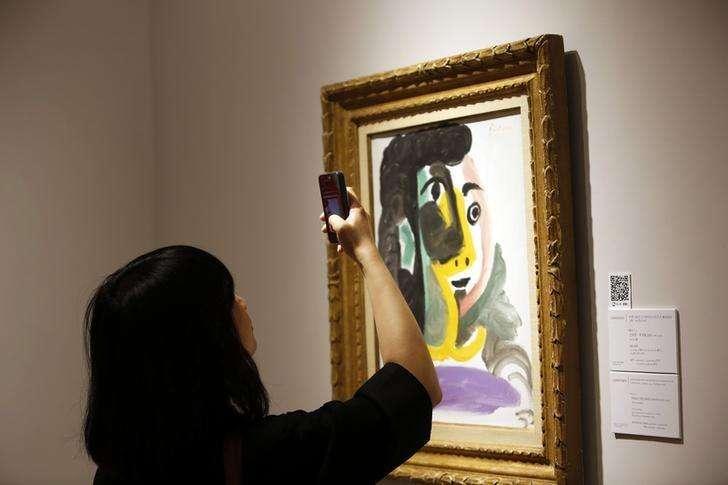 """Mulher tira foto da obra """"Tete de femme"""" antes de um leilão da Christie's, em Xangai, na China. 24/05/2014. Foto: Aly Song/Reuters"""