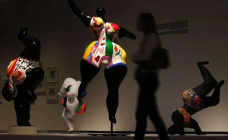 "A visitor walks past the sculptures ""Nana Danseuse Noire"" (2ndL) and ""Nana Noire Upside Down"" (R) by French artist Niki de Saint Phalle (1930-2002) during an exhibition at the Grand Palais Museum in Paris, September 16, 2014. Foto: Christian Hartmann/Reuters"