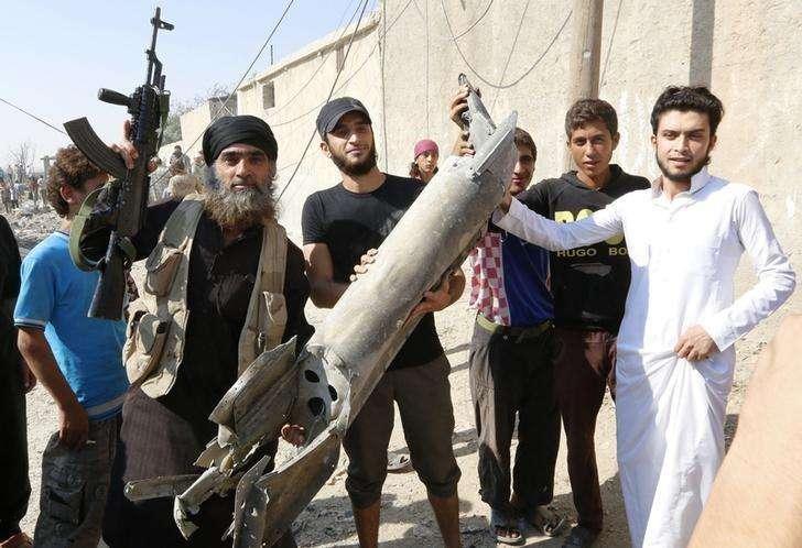 Militante do Estado Islâmico segura peça de avião militar sírio ao lado de moradores de Raqqa, no norte da Síria. 16/09/2014 Foto: Stringer/Reuters