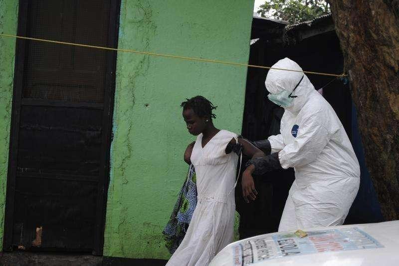 La epidemia de ébola surgida en África Occidental ha causado la muerte de 2.461 personas hasta el momento, la mitad de los 4.985 casos registrados oficialmente, en una crisis sanitaria que no tiene precedente en los tiempos modernos, dijo el martes el director adjunto de la Organización Mundial de la Salud (OMS). En la imagen, un trabajador de la salud lleva a una mujer sospechosa de haber contraído el ébola hasta una ambulancia en Monrovia, el 15 de septiembre de 2014. Foto: James Giahyue/Reuters