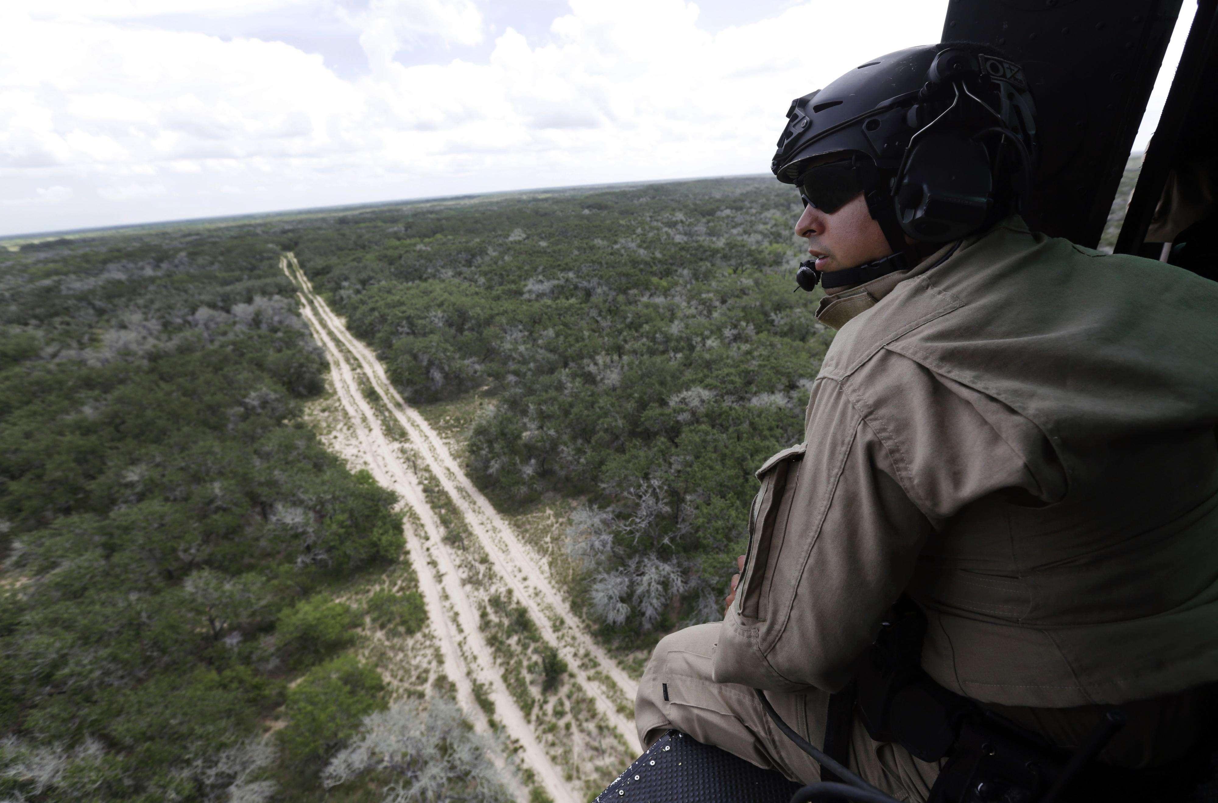 un agente de la Patrulla Fronteriza de Estados Unidos observa desde la portezuela de un helicóptero durante un vuelo cerca de la frontera con México en el área de McAllen, Texas. Foto: AP en español