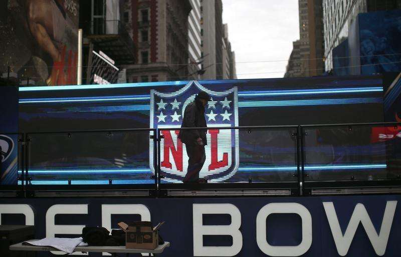 A worker walks on a stage in front of the NFL logo in New York's Times Square January 27, 2014. Foto: Mike Segar/Reuters