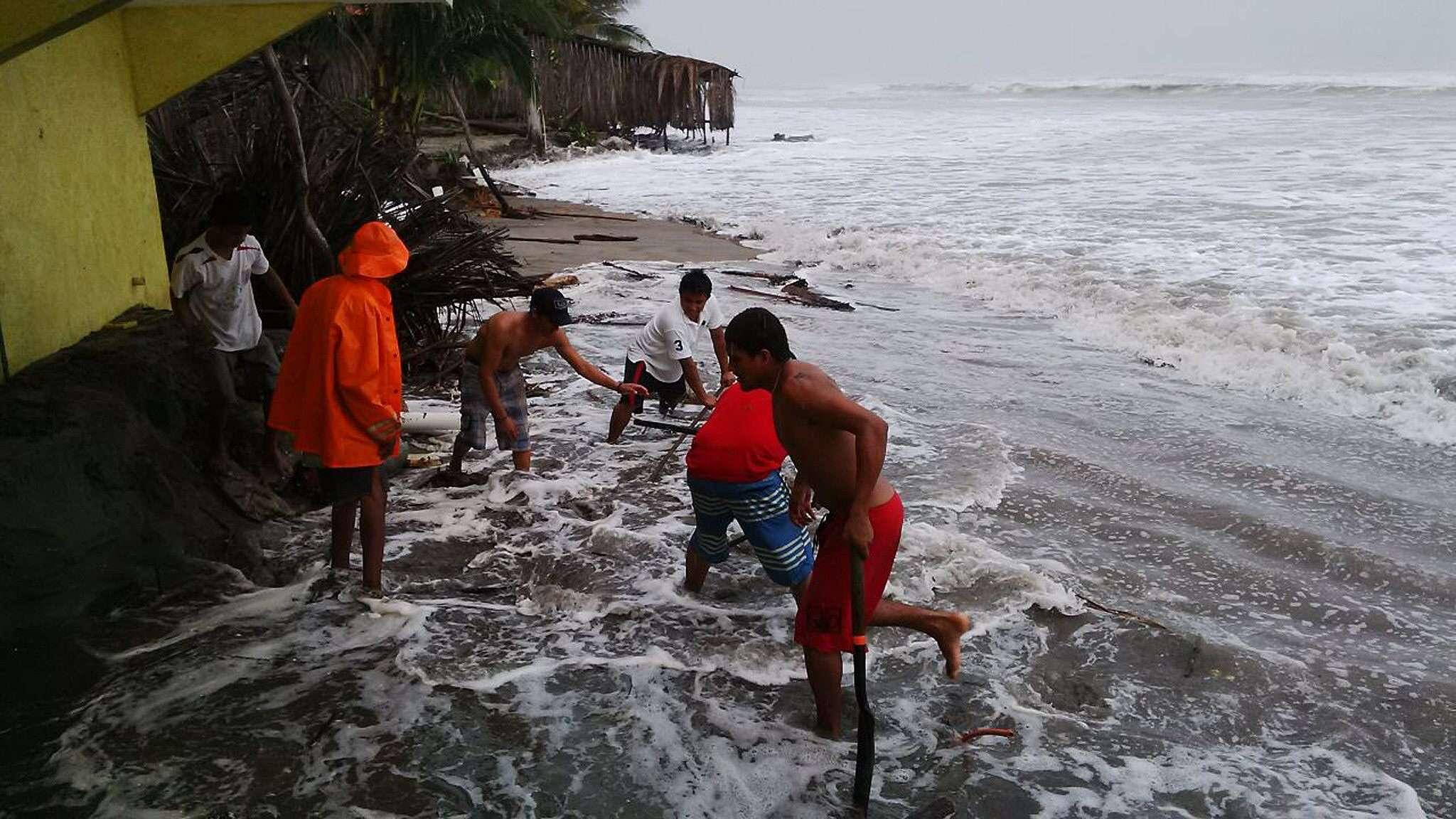 """Habitantes de Acapulco intentan proteger sus pertenencias de las fuertes olas propiciadas por la tormenta """"Polo"""" Foto: EFE"""