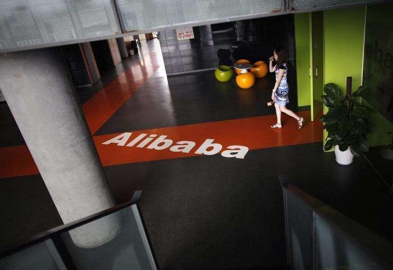 Un empleado pasa sobre un logo de Alibaba en sus oficinas en Hangzhou. Imagen de archivo, 20 junio, 2012. La gigante minorista china Alibaba tiene previsto vender unos 22.000 millones de dólares en acciones el jueves, coronando un proceso de dos semanas que generó un interés febril de inversores de todo el mundo y que podría convertirse en la mayor oferta pública inicial (OPI) de la historia. Foto: Carlos Barria/Reuters