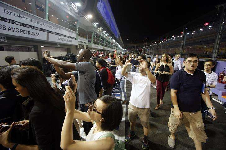 Fans take photos in the pit during a pit walk ahead of the Singapore F1 Grand Prix night race September 18, 2014. Foto: Edgar Su/Reuters