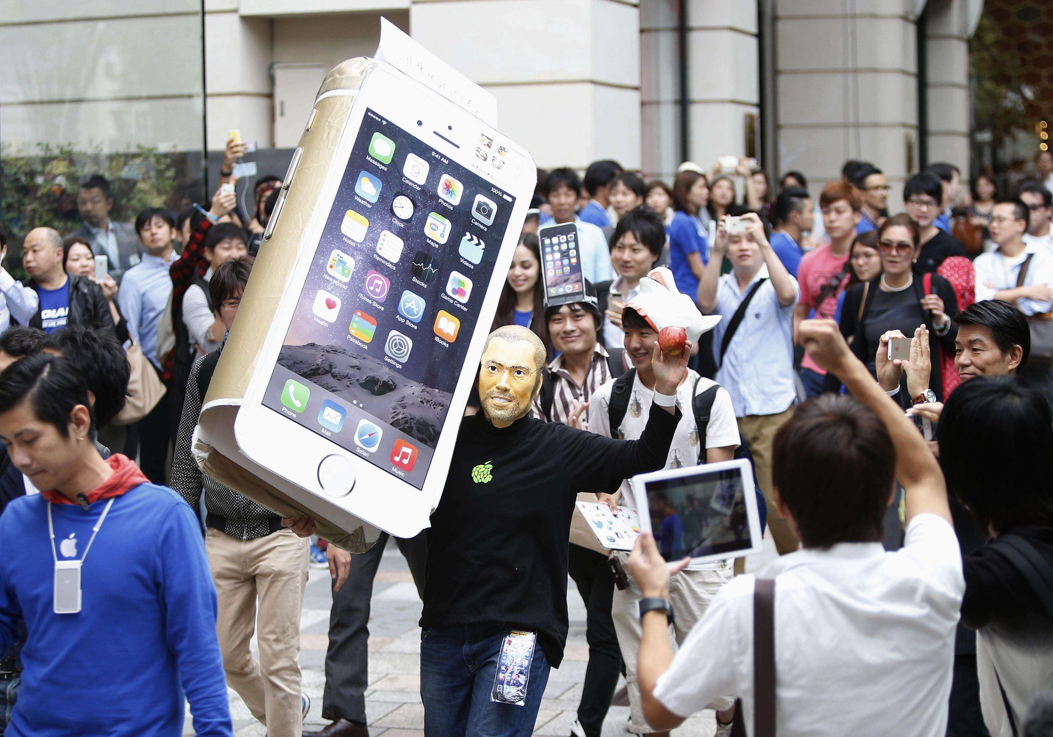 """No Japão, humor deu o tom da fila de espera; homem com máscara do Steve Jobs passeia com um iPhone 6 """"gigante"""" de papelão nas ruas de Tóquio Foto: Yuya Shino/Reuters"""