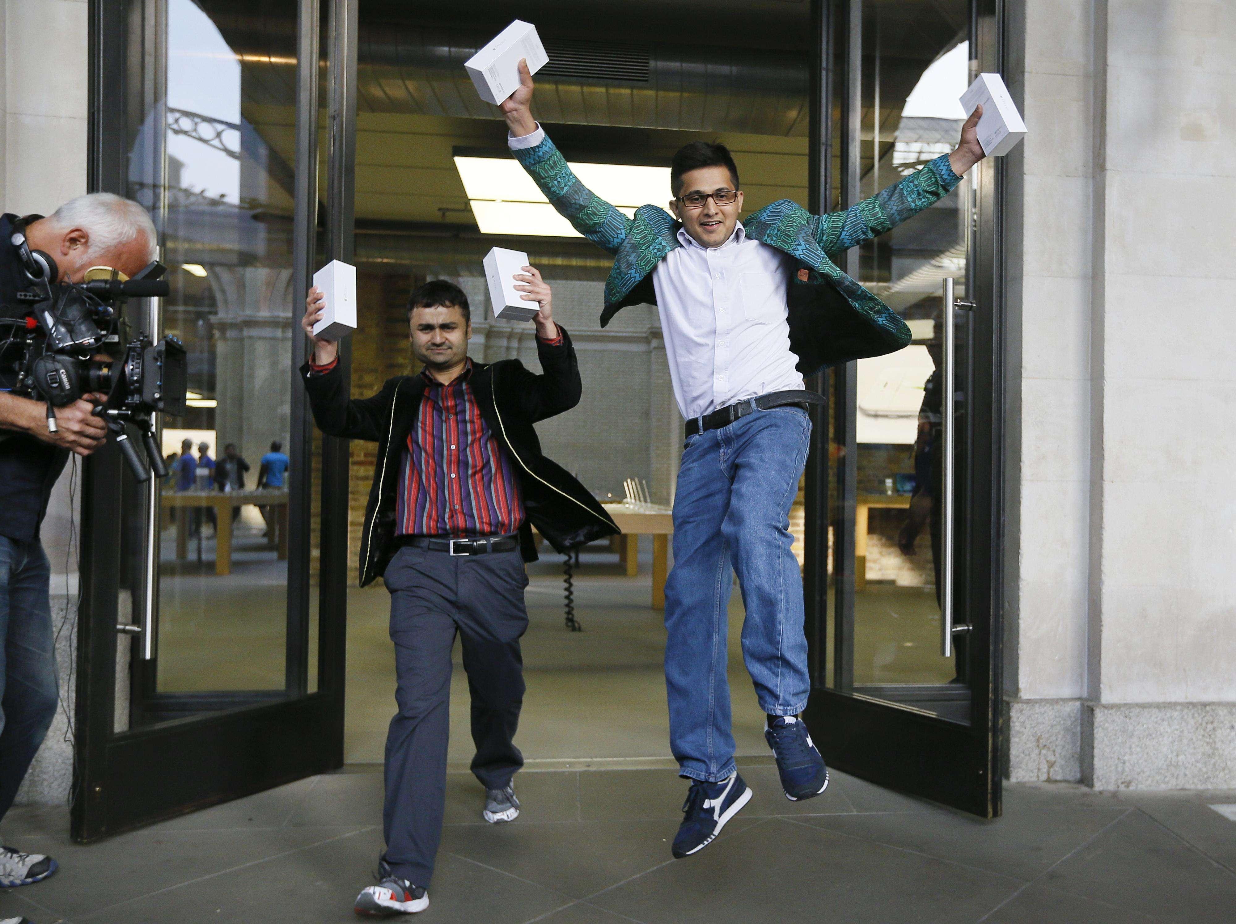 Los primeros compradores salen de una tienda Apple, en Londres, este viernes 19 de septiembre de 2014. Foto: AP en español
