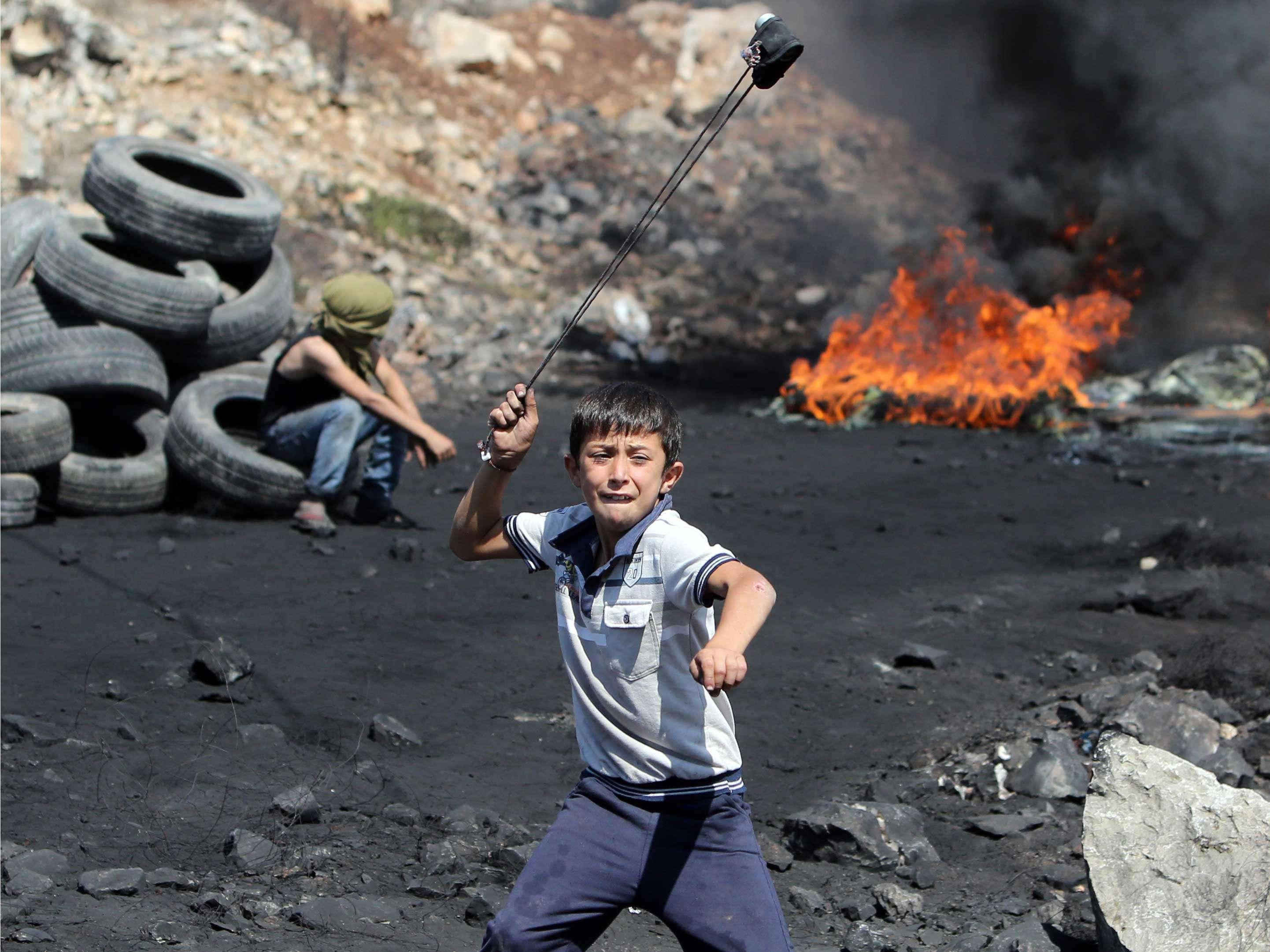 Un joven palestino arroja piedras a las fuerzas de seguridad israelíes durante un choque a raíz de una protesta en la aldea de Kfar Qaddum, en Cisjordania. Foto: AFP en español